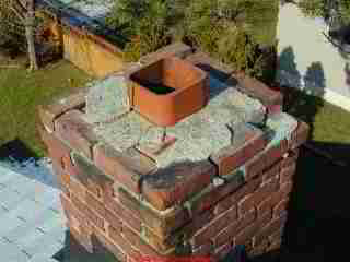 Photograph of a cracked chimney top crown and no cap installed.