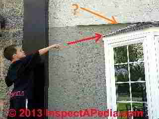 Tanner Daniel Gilligan points out a subsitution for roof-wall flashing over a bay window: the installer tried a wavy line of white caulk aghainst the gray stuco exterior. (C) Daniel Friedman Tanner Gilligan 2013