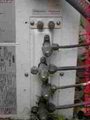Photograph of the high and low pressure air conditioning refrigerant lines and service ports on an air conditioning compressor/condenser
