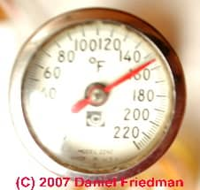Photograph of a dial thermometer reading a high output temperature at an air conditioning compressor