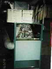 Photograph of older side-vent combination hot air furnace and central air conditioning system. The evaporator coil or A-coil is visible in the top of the unit.