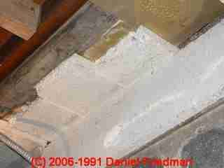 Photograph of  LARGER IMAGE - asbestos slab ceiling insulation, tremolite asbestos showing exposed ends projecting over a basement partition