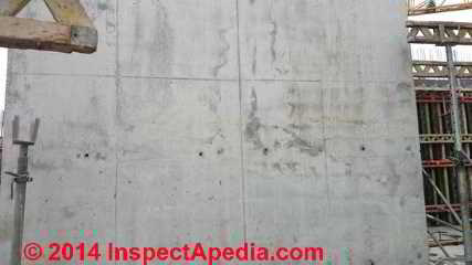 Dark areas suggesting cold pour joints in a concrete wall (C) InspectAPedia CI