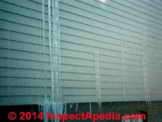 Ice forms at water exiting from vinyl siding due to roof ice dam leaks from above (C) Daniel Friedman